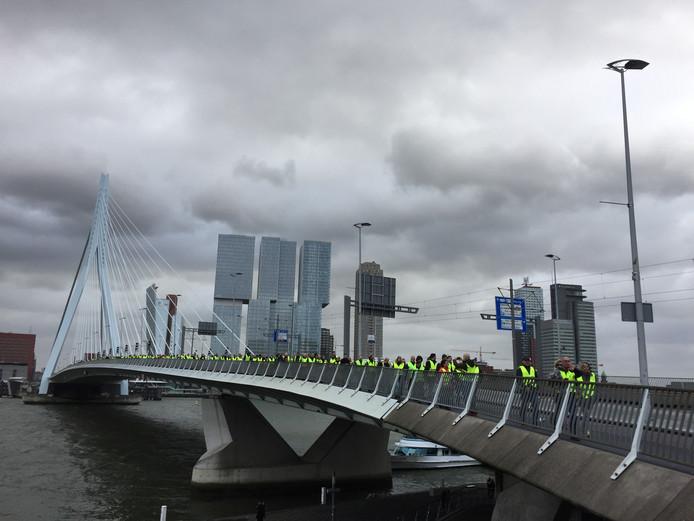 Een stoet van 'gele hesjes' loopt over de Erasmusbrug.