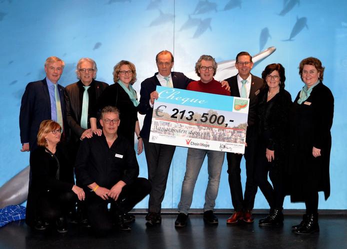 De koren haalden een bedrag van 213.500 euro op voor onderzoek tegen alvleesklierkanker. Casper van Eijck en Peter Overduin (met rode trui) hebben de cheque in handen.