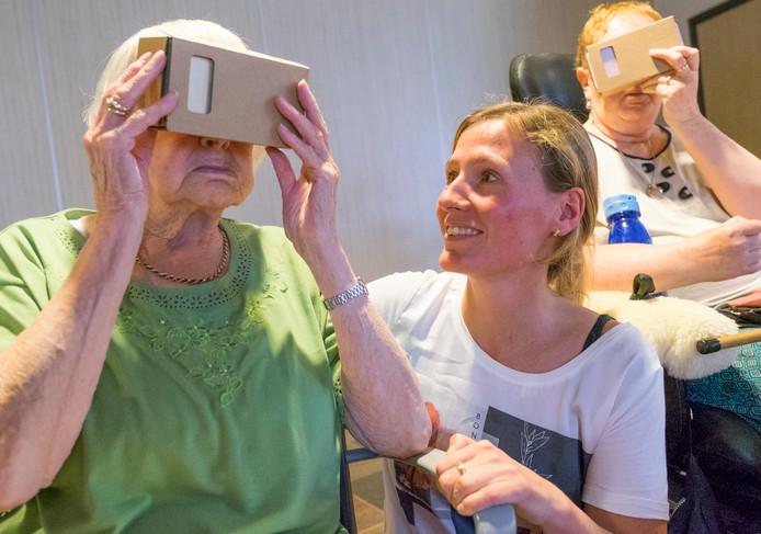 Mevrouw Kole probeert de VR-bril met wat hulp van Marloes Henderikx.