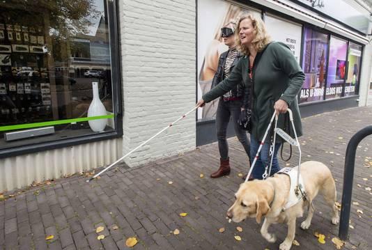 Verslaggever Elke Agten (l) ervaart hoe het is om je als blinde door het verkeer te moeten begeven.