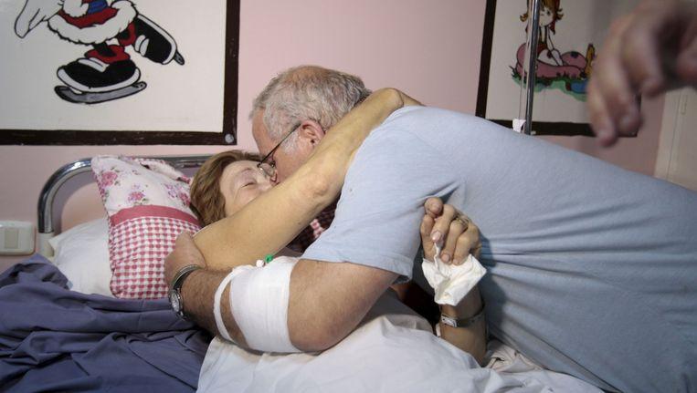 De 62-jarige Criss Callaghan raakte gewond aan haar dijbeen, maar heeft haar leven te danken aan haar brillendoos. Ze wordt geknuffeld door haar man in het ziekenhuis.