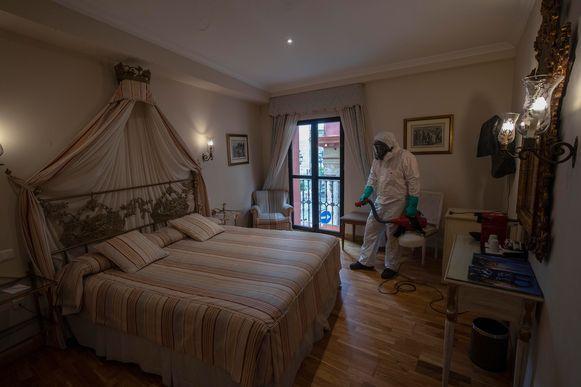 Een medewerker desinfecteert een kamer in Hotel Dona Maria in Sevilla.