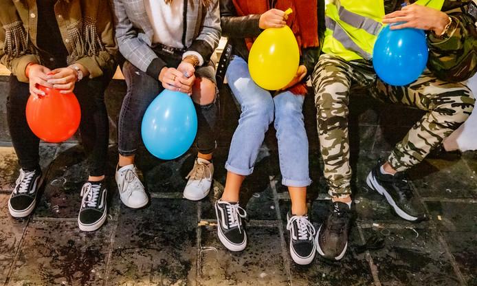 Jongeren die op straat in Amsterdam lachgas gebruiken.