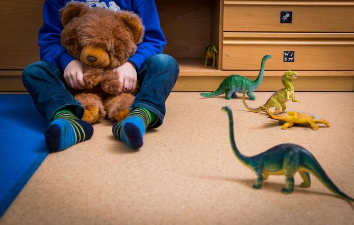 Een jongen met een knuffelbeer in een speelkamer van een jeugdhulpverleningscentrum. (archieffoto)