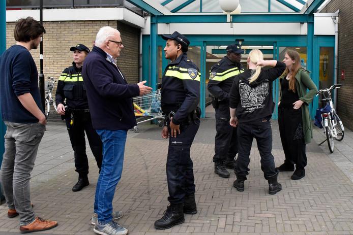 De wijkagenten Jolanda Kloosterziel (l) en Marc Roemer (m) in gesprek met bezoekers van Tournoysveld. Rechts hun 'coach' Iwan Esajas.