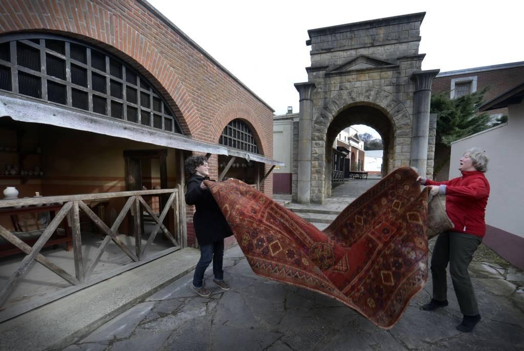 Medewerkers van Museumpark Orientalis kloppen het kleed uit. foto Do Visser/De Gelderlander