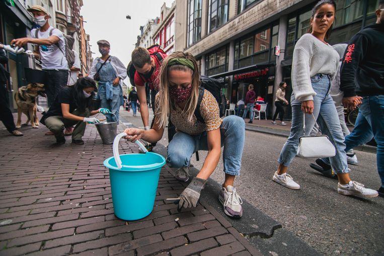 Vrijwilligers rapen peuken op van de straat op de Nieuwendijk in Amsterdam-Centrum. Beeld Reinier van Oorsouw