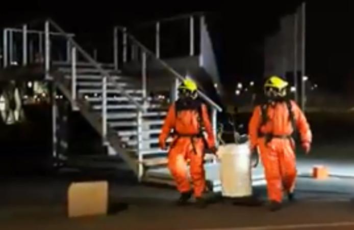 Brandweerlieden vervoeren het afvalvat naar een veilige plek.