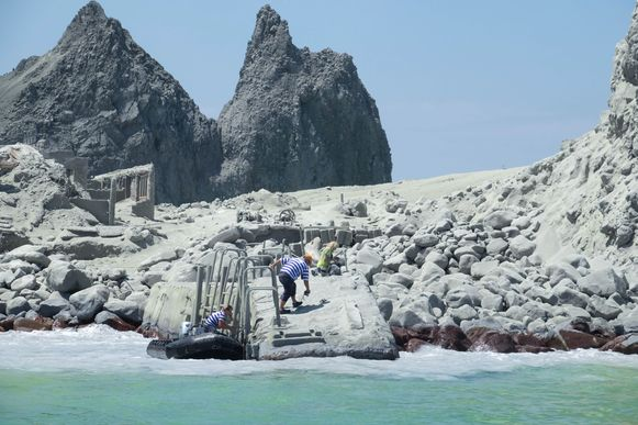 Toeristen en gidsen (met streepjes t-shirt) gaan terug White Island op om mensen te helpen.