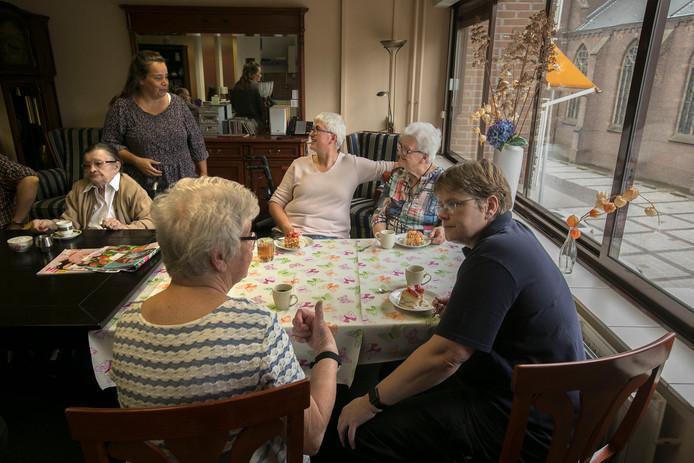 Nellie (linksvoor) in gesprek met Janneke, de dochter van Frieda tegenover haar. Daarnaast dochter Karin. Staand woonbegeleidster Mary, zittend Lucy.