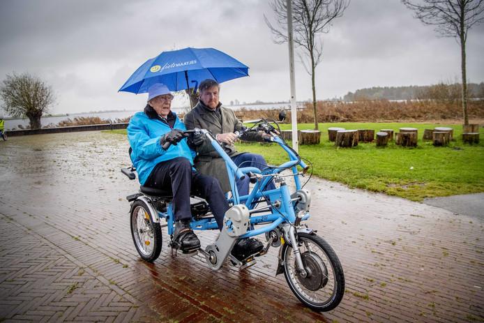 2019-11-28 14:49:53 WARMOND - Koning Willem-Alexander op de duofiets tijdens een werkbezoek aan de Stichting Fietsmaatjes.
