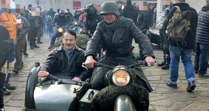 L'homme, clairement grimé pour ressembler au dirigeant nazi, est assis comme passager dans un side-car.