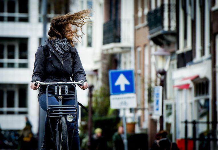 Een vrouw trotseert op haar fiets de wind in Amsterdam Beeld ANP