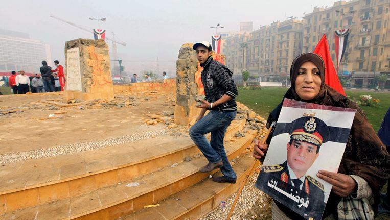 Een vrouw houdt een foto van generaal El-Sissi omhoog voor het vernielde monument op het Tahrirplein Beeld AP