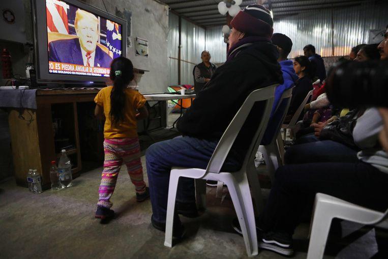 Migranten in Tijuana (Mexico) kijken naar de tv-toespraak van president Trump van dinsdag.  Beeld Getty Images