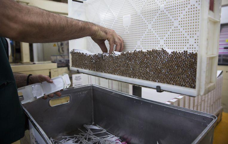 Een werknemer in een fabriek in Servië pakt sigaretten in.    Beeld Bloomberg via Getty Images