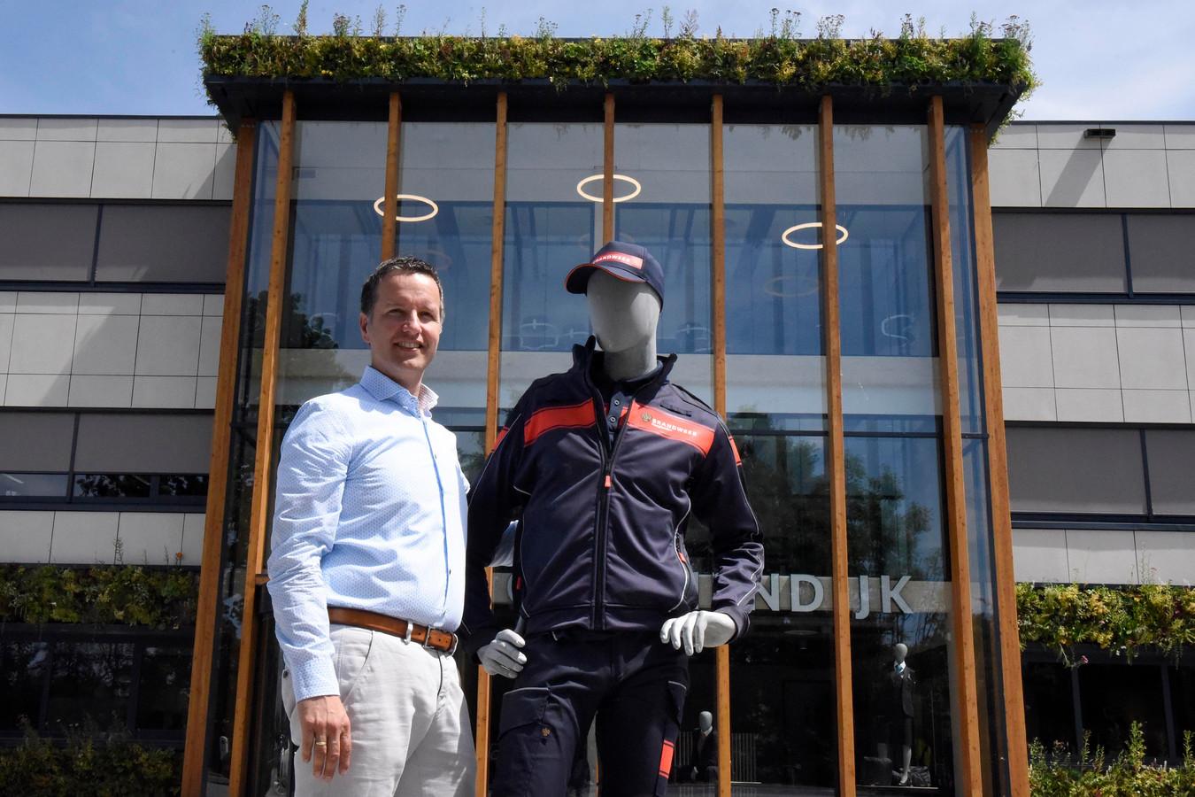 Directeur Marien Groenendijk voor het nieuwe bedrijfspand aan de Carrosserieweg. De paspop draagt het nieuwe uniform van de brandweer Haaglanden.