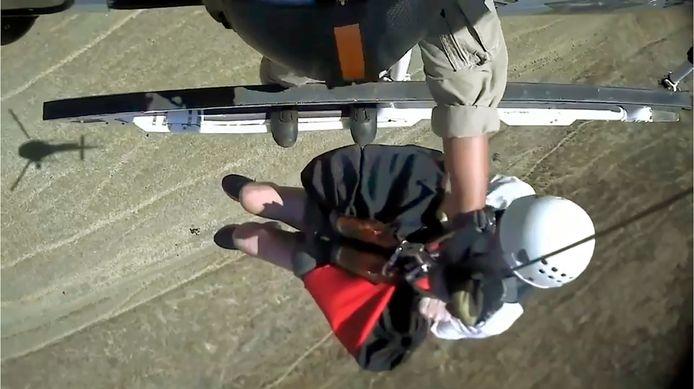 De vrouw wordt door de helikopter gered.
