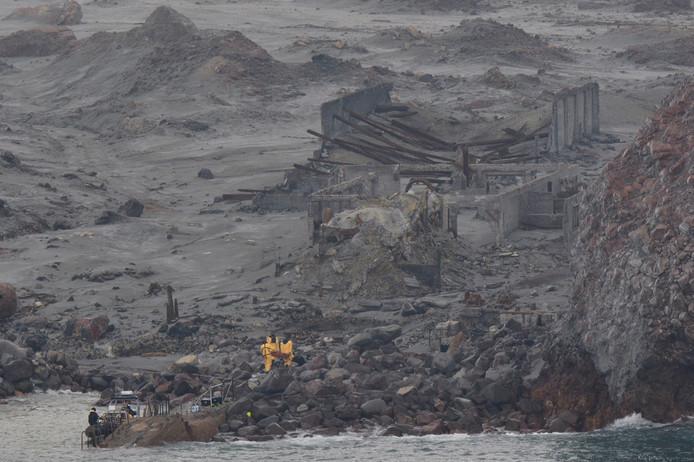 Reddingswerkers op het eiland proberen de achtergebleven lichamen terug te halen.