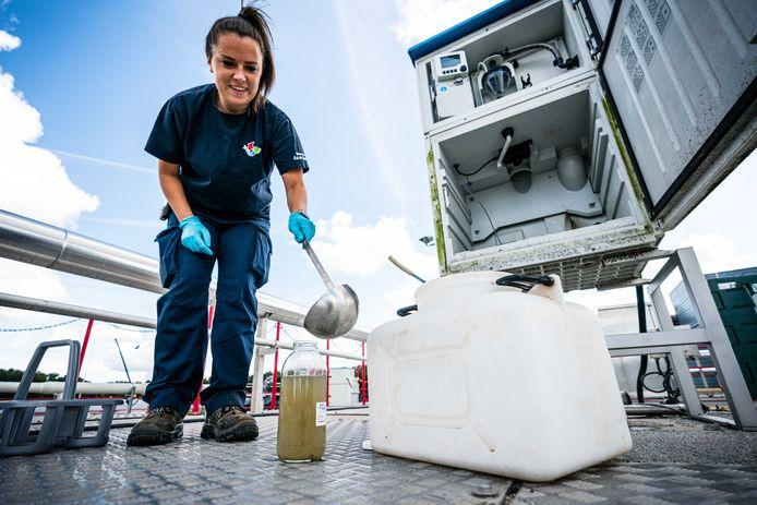 Een medewerker van de rioolwaterzuivering neemt een monster van het rioolwater. Het water wordt onderzocht op onder meer virusdeeltjes om te kunnen vaststellen hoeveel mensen coronaonder de leden hebben en kunnen overdragen.