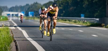 Deelnemers Triathlon Noordoostpolder zoeven over brede asfalt van N50
