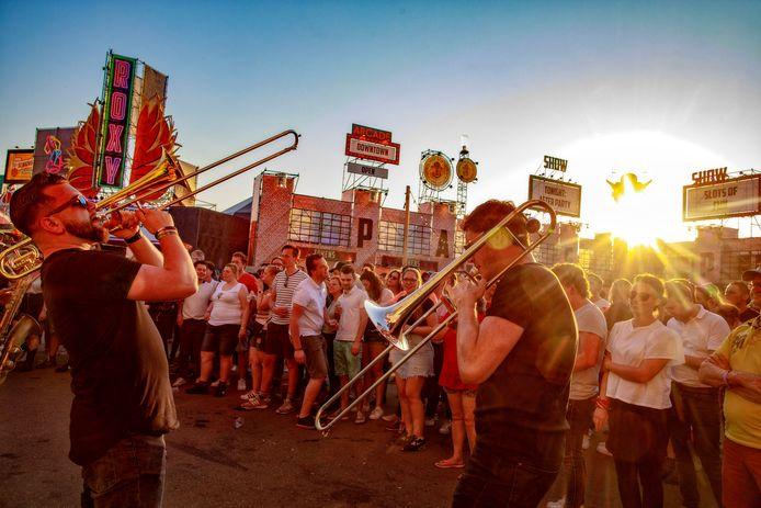Het publiek geniet van de muziek als de zon langzaam achter het festivalterrein verdwijnt.