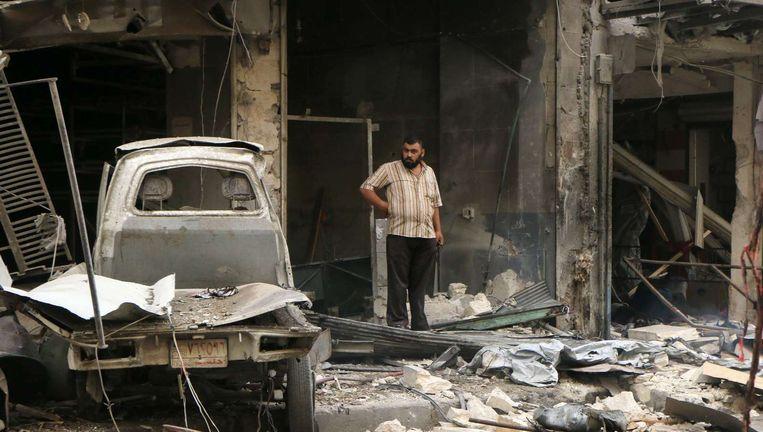 Een Syrische man bekijkt het puin na een bombardement op Aleppo, archiefbeeld. Beeld afp