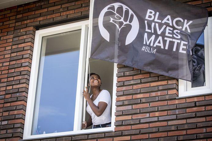 Confiance Ndeze steekt in haar huis in Losser de zelf ontworpen vlag vast even uit. Ze hoopt dat veel mensen op 17 augustus, de door haar zelf geplande actiedag, haar voorbeeld volgen.