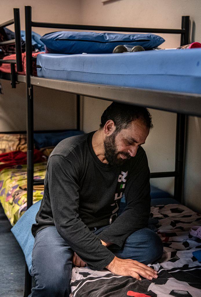 Vader Ahmad op het bed van zijn overleden zoon Ali in het azc in Gilze.