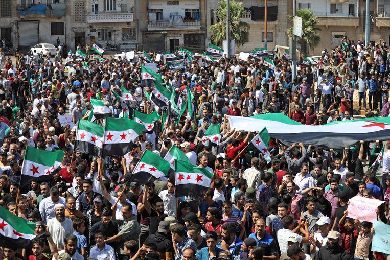 Betogers dragen vlaggen van oppositiegroepen en spandoeken met opschriften