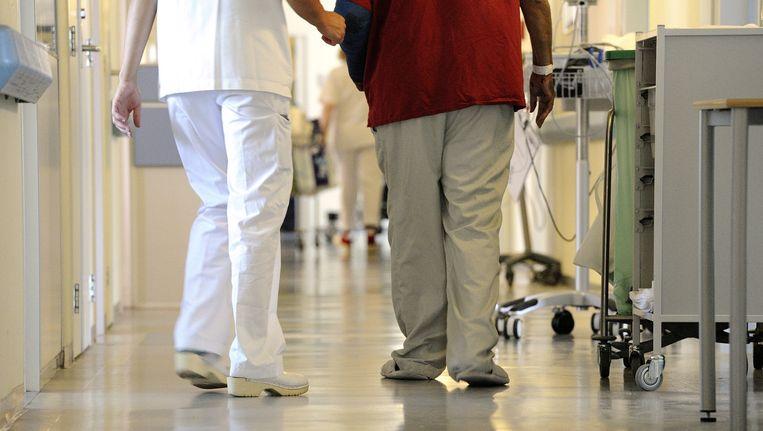 Een verpleegkundige begeleidt een patiënt. Beeld ANP