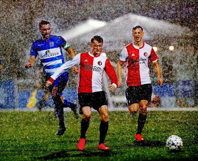 PEC Zwolle-verdediger Bram van Polen (links) probeert in de stromende regen Feyenoorder Sam Larsson tot stoppen te dwingen.