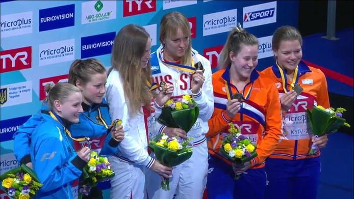 Daphne Wils (uiterst rechts) en Inge Jansen met hun bronzen medaille van het EK synchroonspringen in Kiev.