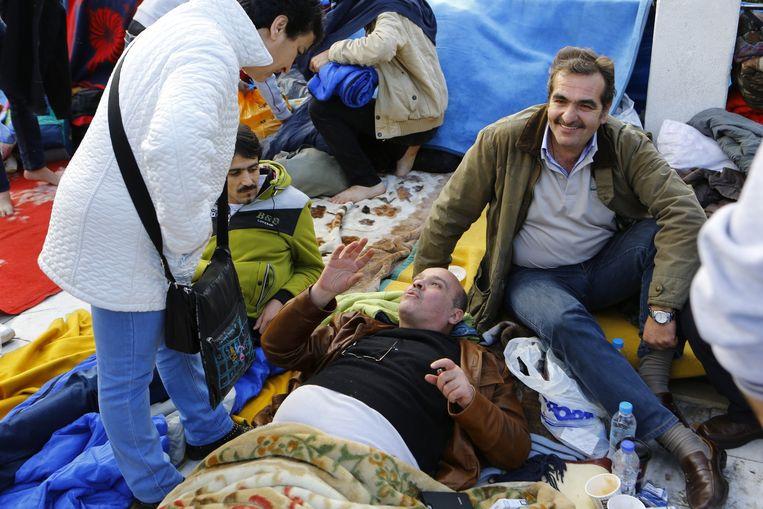 De Griek Ioannis Michelogiannakis (lid van het Parlement) ligt op de grond en vergezelt de Syrische vluchtelingen die op het Atheense Syntagma-plein een hongerstaking houden. 7 december 2014 Beeld Michael Debets / Demotix