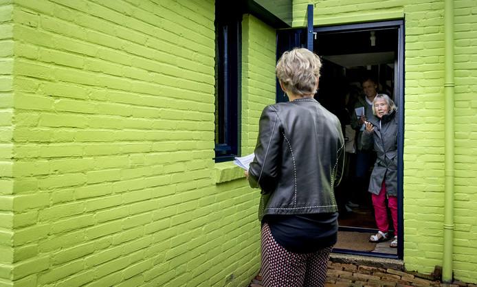 Rechter A.C. Loman neemt samen met Ineke van Amersfoort (R) een kijkje bij het groene huis aan de Pluto in Den Helder.