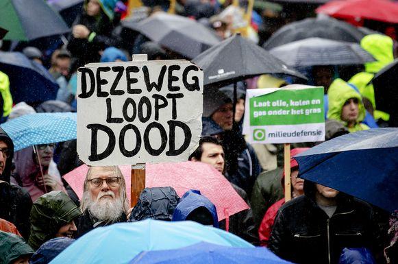 Deelnemers met borden en spandoeken tijdens de klimaatmars. Ze vragen om klimaatactie, door politiek en het bedrijfsleven.