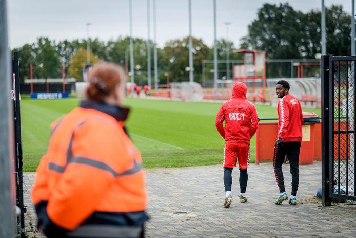 Stewards bewaken de poort bij FC Twente. Er mag niemand anders dan de spelers het trainingsveld op.