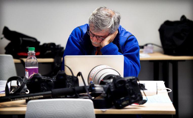 Reuters fotograaf Michael Kooren zit er even helemaal doorheen en is weggedommeld achter zijn laptop. Beeld Klaas Jan van der Weij / de Volkskrant