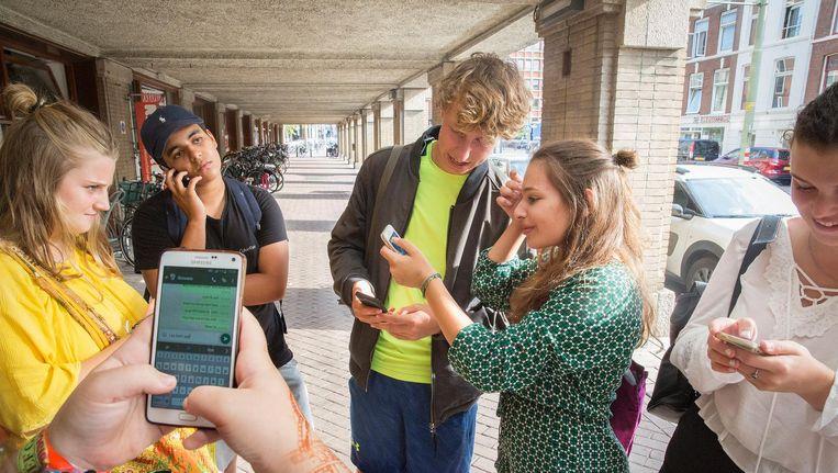 Jongeren op de mobiele telefoon in Den Haag. Beeld Arie Kievit