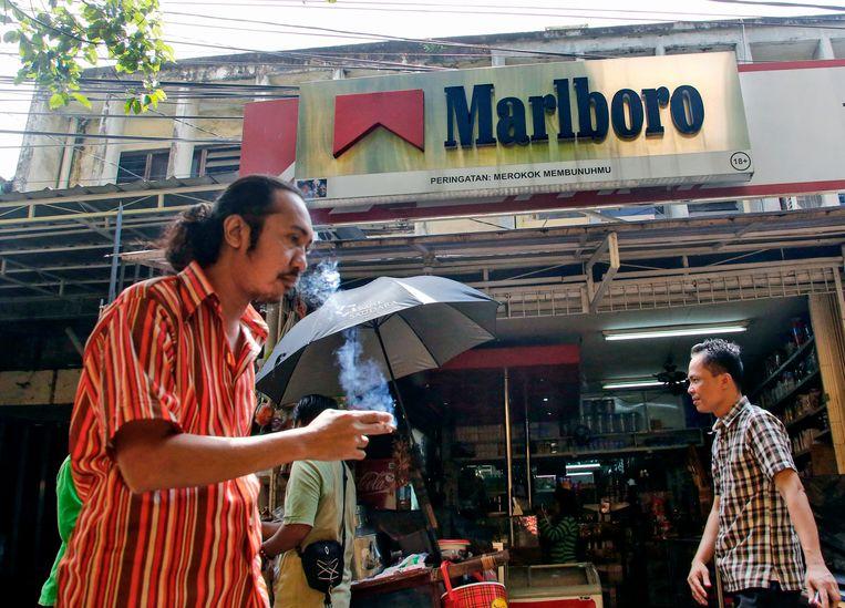 Een roker loopt langs een Marlboro-reclame in de Indonesische hoofdstad Jakarta. Indonesië staat bekend als het Disneyland voor de tabaksindustrie.