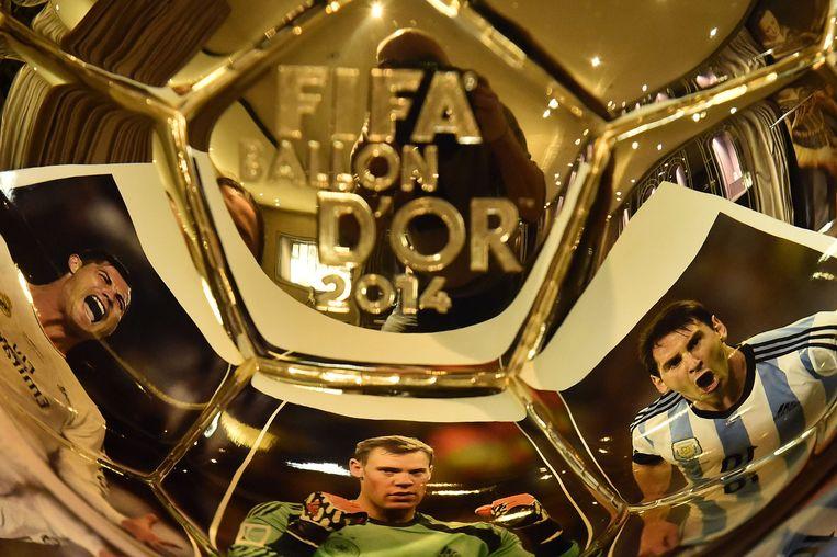Foto's van Christiano Ronaldo, Manuel Neuer en Lionel Messi reflecteren op de Gouden Bal. Beeld afp
