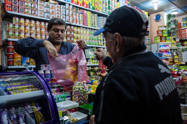 Een klant rekent zijn boodschappen af in een winkel in Bagdad. Middenstanders doen goede zaken met de verkoop van 'nationale producten', een codeterm voor waar die niet uit het buurland Iran komt. Beeld Hawre Khalid