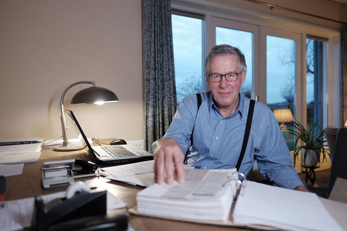 Herman Stapelbroek achter de vele papieren op zijn bureau.