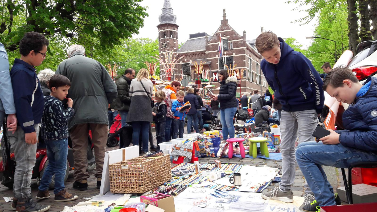 Vrijmarkt op De Lind, tegen het decor van een nostalgische kermis.