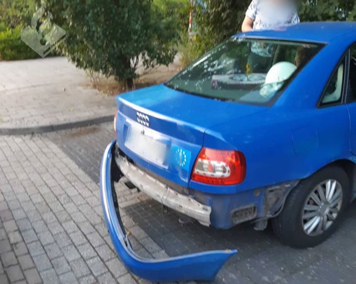 De blauwe auto rijden waarvan de achterbumper half over de weg sleepte.