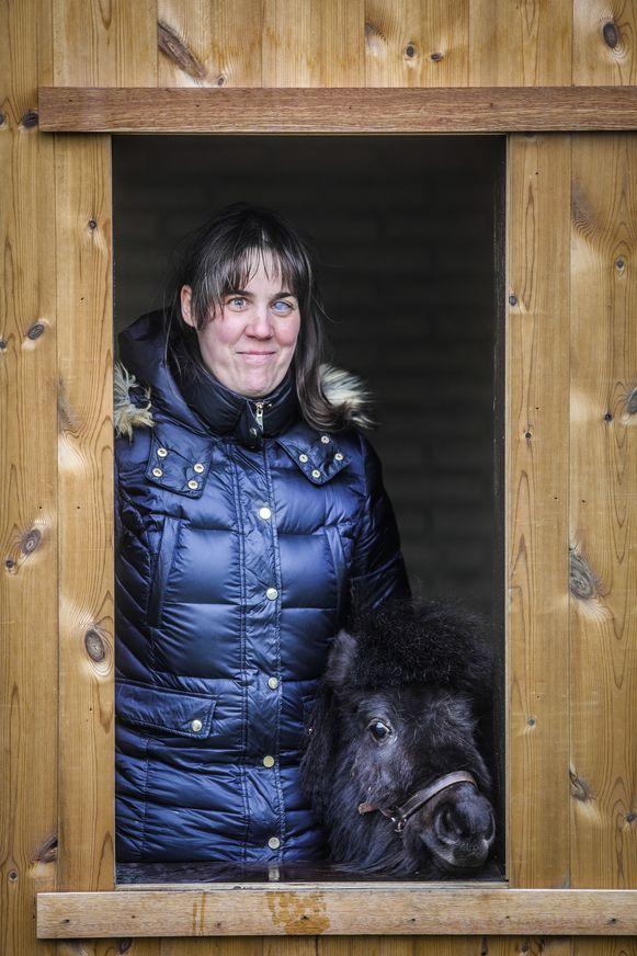 Monique Van den Abbeel met Dinky door het venster van het tuinhuis.
