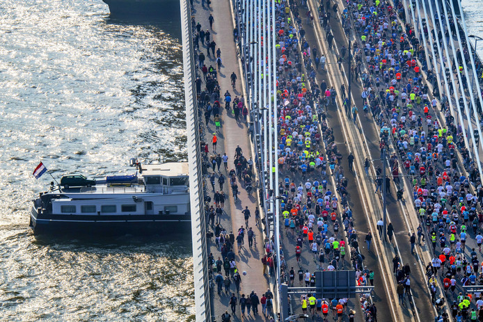 Een schip vaart onder de Erasmusbrug door waar duizenden lopers zijn begonnen met de marathon.