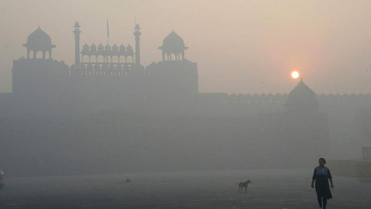 Een Indiase vrouw loopt langs de Jama Masjid in het centrum van Delhi. De stad is volledig gehuld in een zwarte mist. Beeld afp