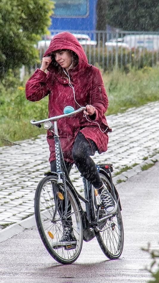 Fietsers op de burg. Broxlaan in Tilburg hadden last van regenbuien en de harde wind.