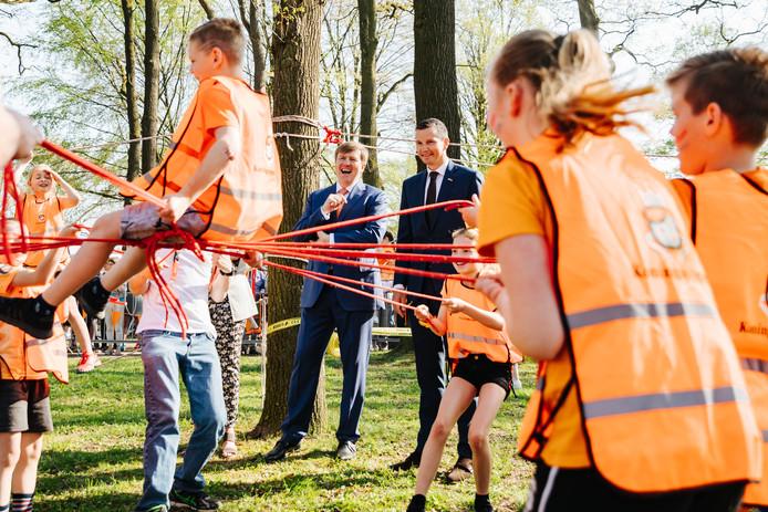 Koning Willem-Alexander en Richard Krajicek kijken toe hoe de leerlingen Binnenstebuiten spelen.